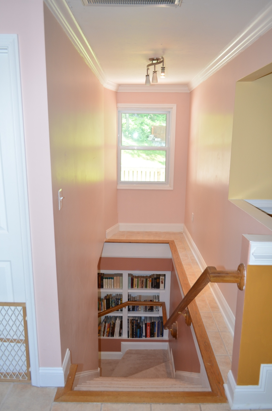 Built-in bookshelves in the basement stairway. The stairway leads from the main level sitting area to the basement foyer and walk-out double door exit.